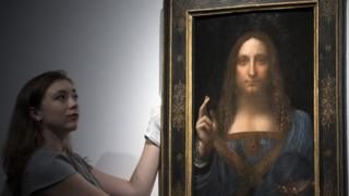 A Christie's staff member posed with Salvator Mundi before the auction
