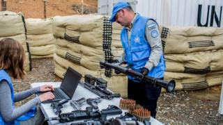Handout photo released by the Revolutionary Armed Forces of Colombia (FARC) of a UN observers checking weapons handed by the FARC as part of the peace process in Buenos Aires, Cauca Department, 14 June 2017