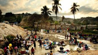 Haitians bathe and wash clothes in a stream on the one-year anniversary of the 2010 earthquake