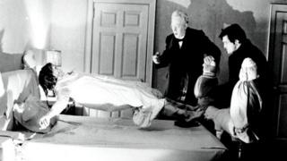 still from The Exorcist in which a girl is levitating as two men watch, looking shocked
