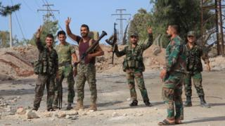 Syrian soldiers celebrate on 4 September 2016 in the southern outskirts of the Syrian city of Aleppo