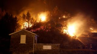 Firefighters work to save a house from a forest fire in Carvalho, near Gois, Portugal, June 19, 2017