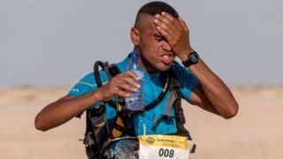 Mohamed el-Morabity kutoka Morocco, anajimwagilia maji usoni alipokuwa anakimbia na kushinda mbio za marathon za El Djerid katika nyikakatika mji wa Tozeur.