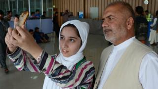 Afghan teenager Fatemah Qaderyan takes a photograph with her father at Herat airport on on July 13, 2017