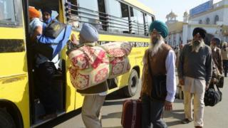 Indian Sikh pilgrims prepare to board a bus at the railway station in Amritsar (25 November 2012)