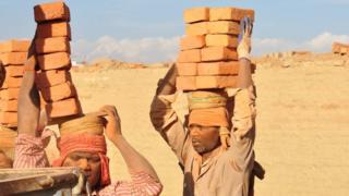 عمال يحملون الطوب