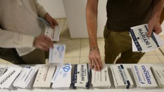 French residents pick up their ballots before casting their vote in the French legislative elections at the French embassy in New Delhi on 4 June 2017