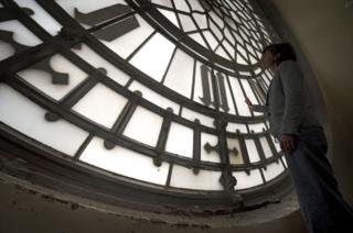 A woman inspects a the clock face.