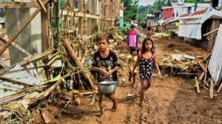 Children walk past debris and damaged houses trees in Barangay San Mateo Borongan in eastern Samar on 17 December 2017, after Tropical Storm Kai-Tak blew through the area