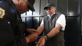 A police officer removes handcuffs from Benedicto Lucas Garcia, a former army commander credited with founding Guatemala's paramilitary groups, before escorting Lucas Garcia into a courtroom in Guatemala City, Wednesday, Jan. 6, 2016.