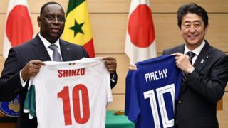 """Senegal""""s President Macky Sall (L) and Japan""""s Prime Minister Shinzo Abe (R) exchange national soccer jerseys at the end of a joint press conference at the Prime Minister""""s official residence in Tokyo, Japan, 13 December 2017."""