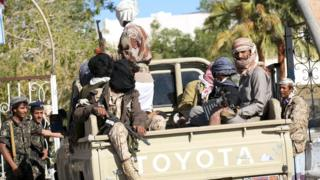 Fighters loyal to Yemen's government ride on the back of a truck