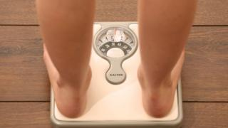 Young girl weighing herself on bathroom scales, checking her weight