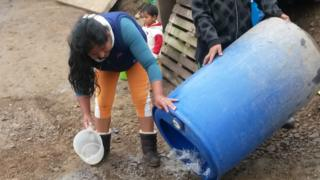 Residents of Nueva Rinconada clean out their water tanks