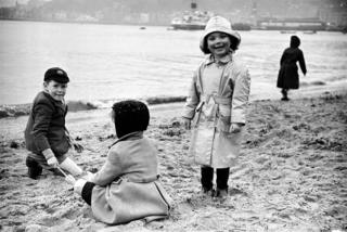 Three kids build a sandcastle in Rothesay in 1955.