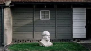 Un busto de Vladimir Lenin frente a una casa