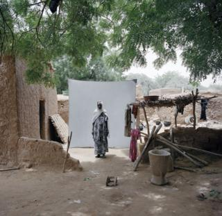 A woman stands in her village.