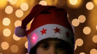 A child attend a ceremony of lighting up the capital's biggest Christmas tree in Sofia
