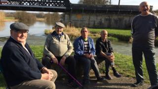 A group of French fishermen sitting by a river