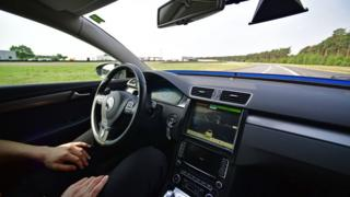 Car driving itself, with man in driver seat doing nothing