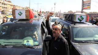 """Mourners carry the Iraqi flag-draped coffins of two protesters killed in the protests outside Baghdad""""s highly fortified Green Zone on Friday, during their funeral procession in Baghdad, Iraq. Saturday, May 21, 2016."""