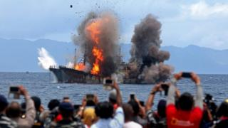 People take pictures of a burning ship as the government destroyed foreign boats at Morela village in Ambon island