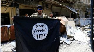 أحد أفراد الأمن العراقي يحتفي بطرد مسلحي تنظيم الدولة الإسلامية من الموصل