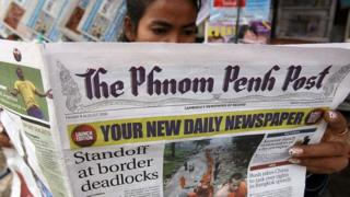 A Cambodian woman reads a copy of the English-language newspaper The Phnom Penh Post at a news stand in Phnom Penh on August 8, 2008.