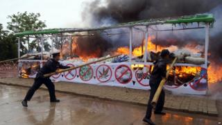 Members of Myanmar fire brigade poke burning narcotic drugs with sticks during a destruction ceremony of seized narcotic drugs in outskirts of Yangon on 26 June