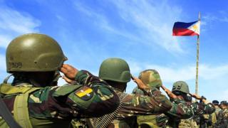 Philippine soldiers salute during a flag ceremony as they end their operation against Islamic militants in Butig Town, Lanao Del Sur on the southern Philippine island of Mindanao on March 1, 2016.