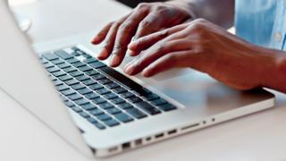 Man typing on macbook