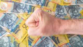 A fist rests on top of several Australian $50 notes