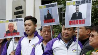 """Members from Civic Party, holding portraits of (L-R) Wang Qingying, Yuan Chaoyang and Tang Jingling, protest outside China""""s Liaison Office in Hong Kong, China, January 29, 2016"""