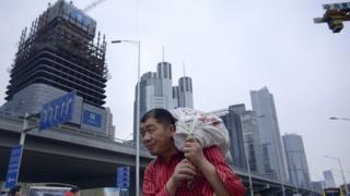 A man carrying a package as he walks through Beijing