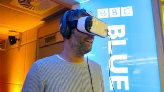 A man watches VR content using the Samsung Gear VR headset