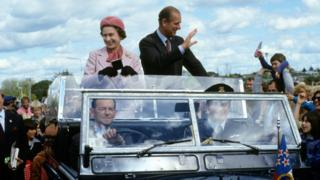 Queen Elizabeth ll and Prince Philip, Duke of Edinburgh wave to well-wishers from their open car in October 1981 in Wellington, New Zealand.