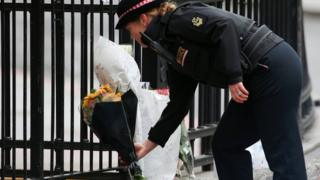 A police officer prepares to lay flowers near London bridge