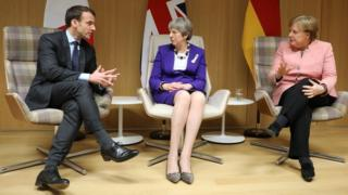 UK Prime Minister Theresa May (C), German Chancellor Angela Merkel (R) and French President Emmanuel Macron (L) give a press conference on March 22, 2018