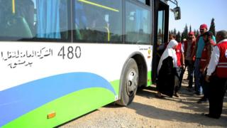 A woman evacuated from the besieged town of Darayya arrives at a government district