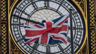 Часы и британский флаг на здании палаты лордов