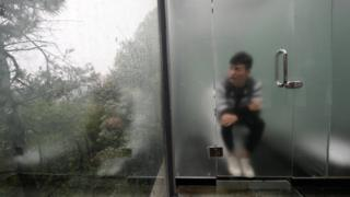 Man sits on toilet, behind lightly frosted glass door, looking out at the forest outside. Changsha, China, 29 September 2016.