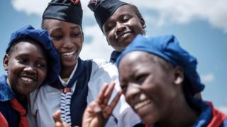 """Members of Kenya Girl Guides take photos after attending ceremony of the International Women""""s day at Kawangware in Nairobi, Kenya, on March 8, 2018"""