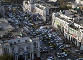 Cars and autorickshaws move through the central Connaught Place area in New Delhi, India, Thursday, Dec. 24, 2015.
