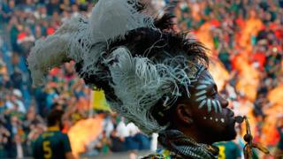 A man in a traditional costume performs ahead of the Rugby test match between South Africa (Springboks) and New Zealand (All Blacks) at Newlands Rugby stadium on October 7, 2017 in Cape Town. / AF