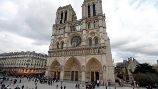 People walk past the entrance to the Notre Dame Cathedral in Paris on 8 February, 2013