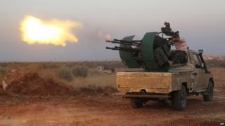 Rebel fighters fire a heavy machine gun during clashes with Syrian pro-government forces on the frontline facing Deir al-Zoghb, a government-held area in the north-western Idlib province, on August 31, 2015.