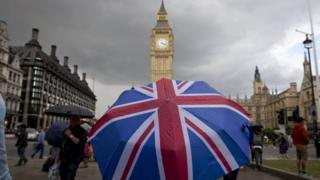 Union flag themed umbrella near Big Ben at the Houses of Parliament in central London on June 25, 2016,