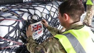 An aid-worker labels supplies with a 'UK aid' sign
