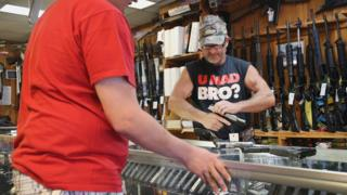 "A man tries a gun in a gun store with a t-shirt saying ""U mad bro?"" and a khaki hat."