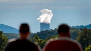 Two men stand facing the cooling tower of the nuclear power plant of Goesgen from the city of Aarau, Switzerland